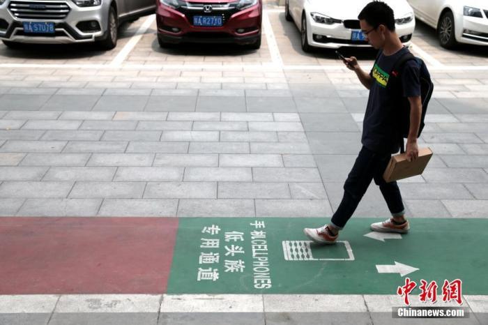 """资料图:西安街头出现一条专为""""低头族""""设计的通道。中新社记者 张远 摄"""