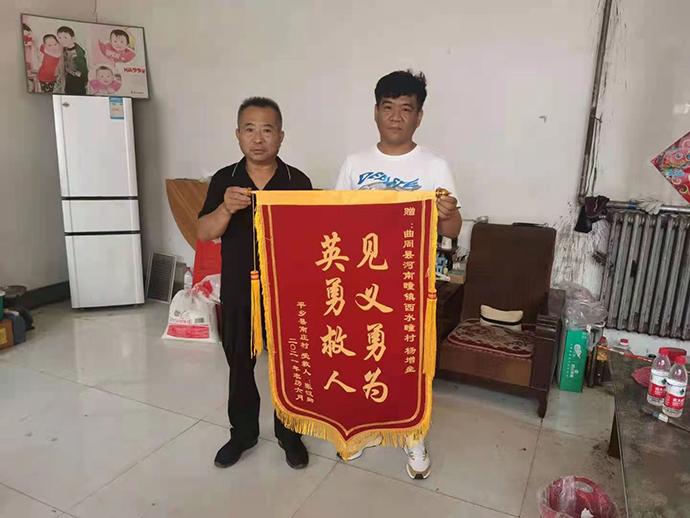 """张贵川把一面写有""""见义勇为,英勇救人""""的锦旗送到曲周县河南疃镇西水疃村杨增垒家中。"""