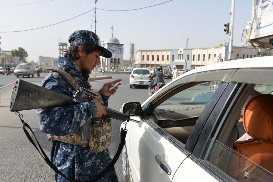 9月11日,在阿富汗坎大哈的一处检查点,塔利班成员查验过往车辆驾驶员的证件。新华社 图