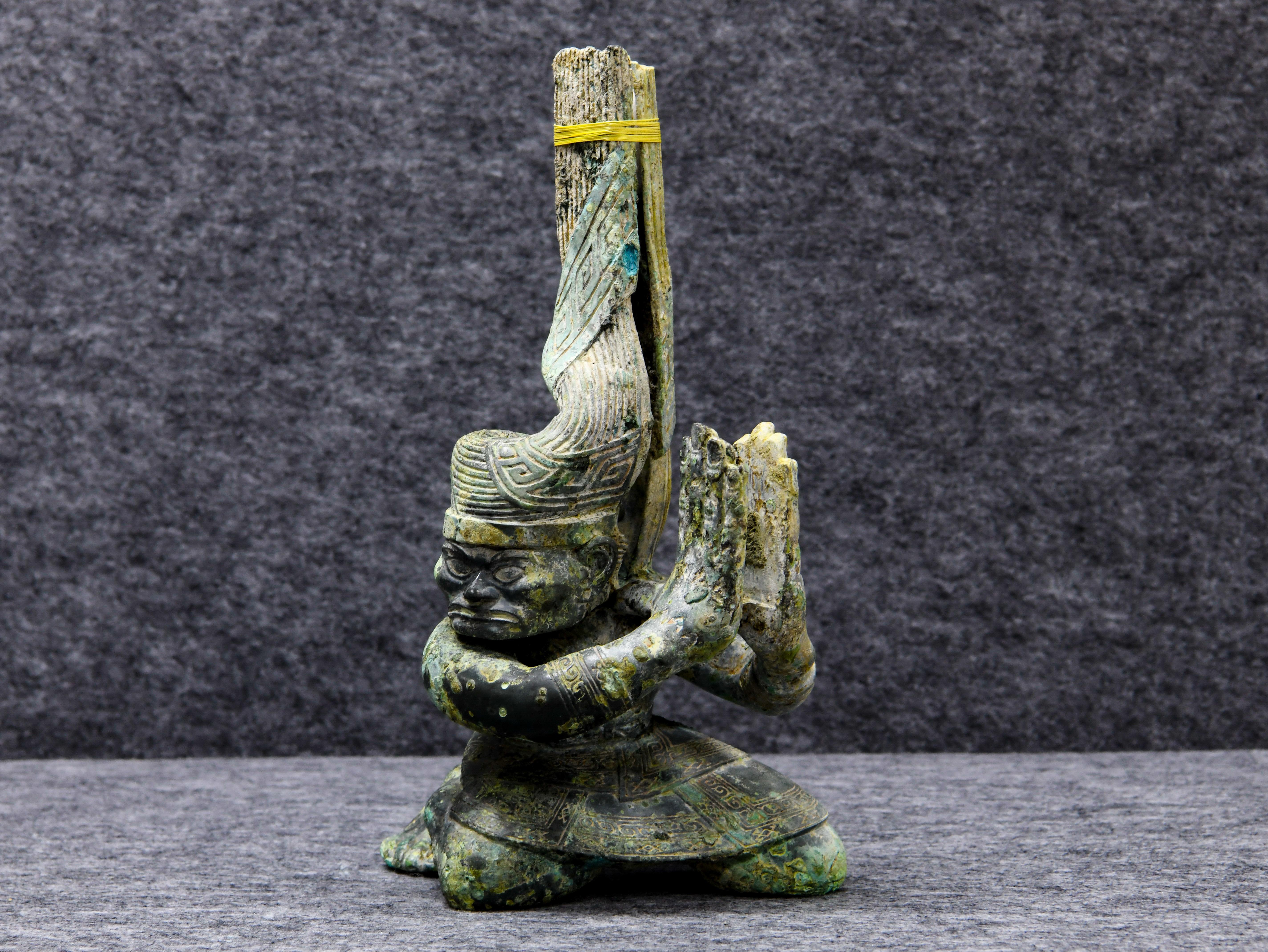 """↑这是9月3日在四川省文物考古研究院三星堆考古研究所拍摄的三星堆遗址4号""""祭祀坑""""出土的铜扭头跪坐人像。新华社记者 王曦 摄"""