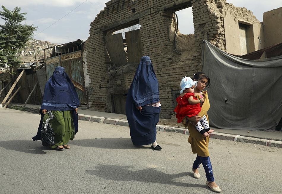 当地时间2021年8月22日,阿富汗首都喀布尔,阿富汗妇女和儿童从街头走过。