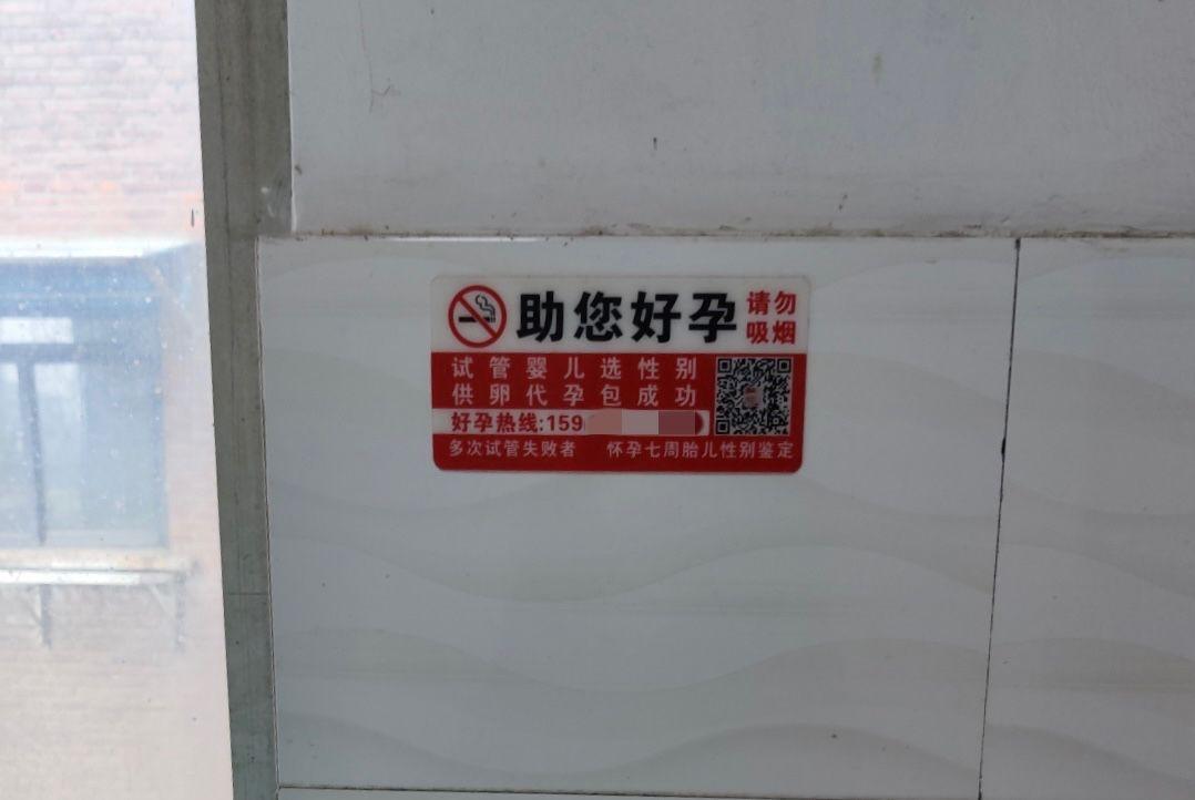 郑大一附院附近的小旅馆内,贴有辅助生殖广告。新京报记者 吴小飞 摄
