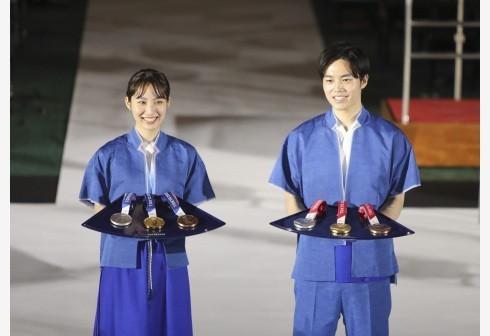 工作人员在发布仪式上展示颁奖志愿者礼服和奖牌托盘