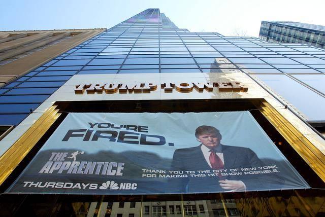 (图说:特朗普通过真人秀《学徒》走红,节目海报悬挂在特朗普大厦外墙。图/The New York Times)