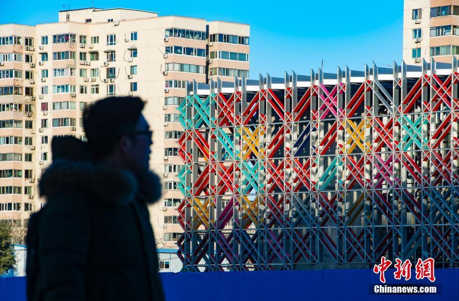 """2020年12月3日,日前完工的北京2022年冬奥会冰球训练场馆——五棵松冰上运动中心的""""冰菱花""""幕墙在阳光的映照下色彩斑斓。 中新社记者 侯宇 摄"""