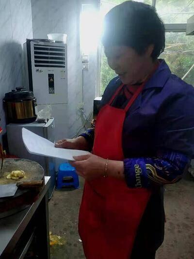 韩仕梅在厨房看自己写的诗。受访者供图