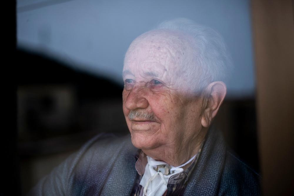 当地时间2021年3月2日,西班牙巴塞罗那,88岁的Jesus Blasco身患喉癌,透过公寓的窗户向外看。