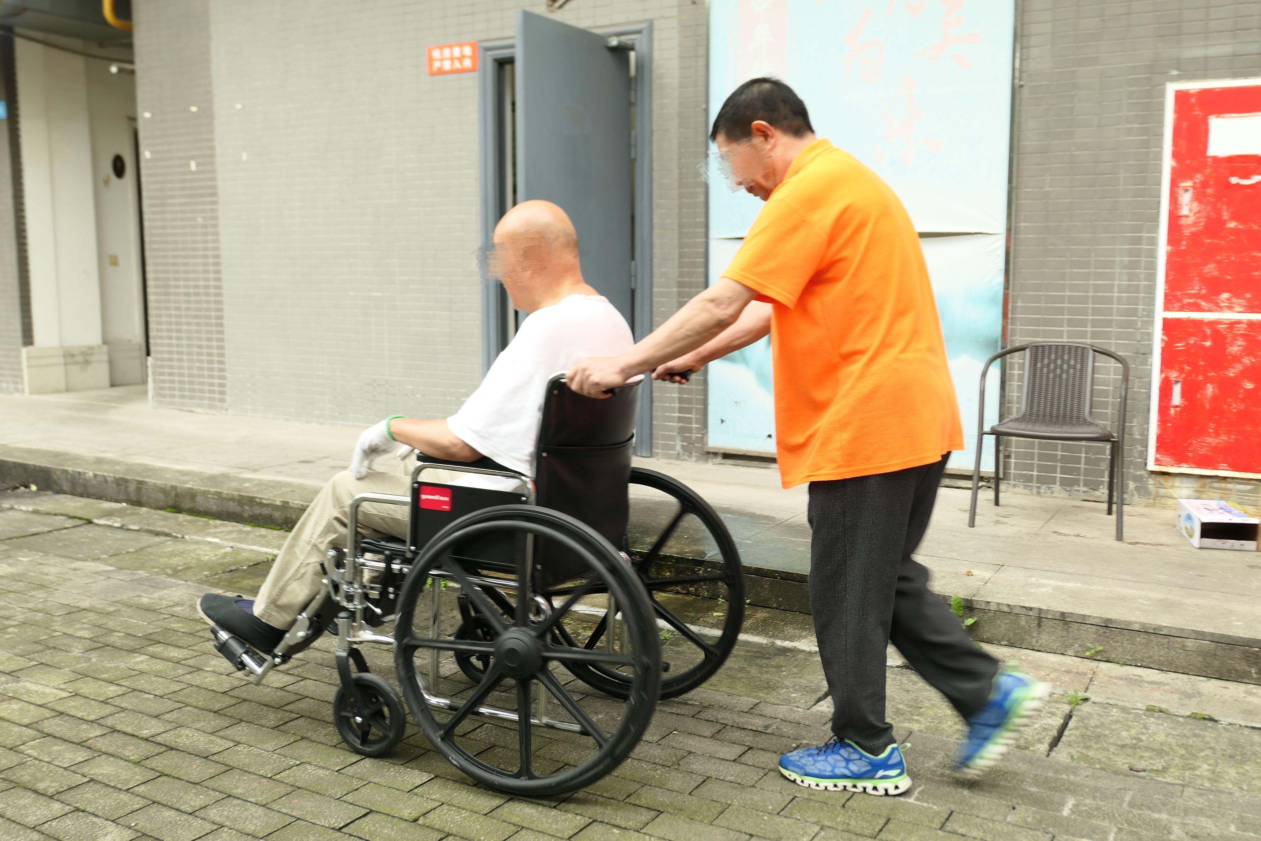 10月5日,养老机构院内,一名护理员推着老人散步。新京报记者 徐杨 摄
