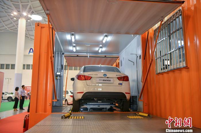 图为一辆纯电汽车正在演示更换蓄电池。 骆云飞 摄