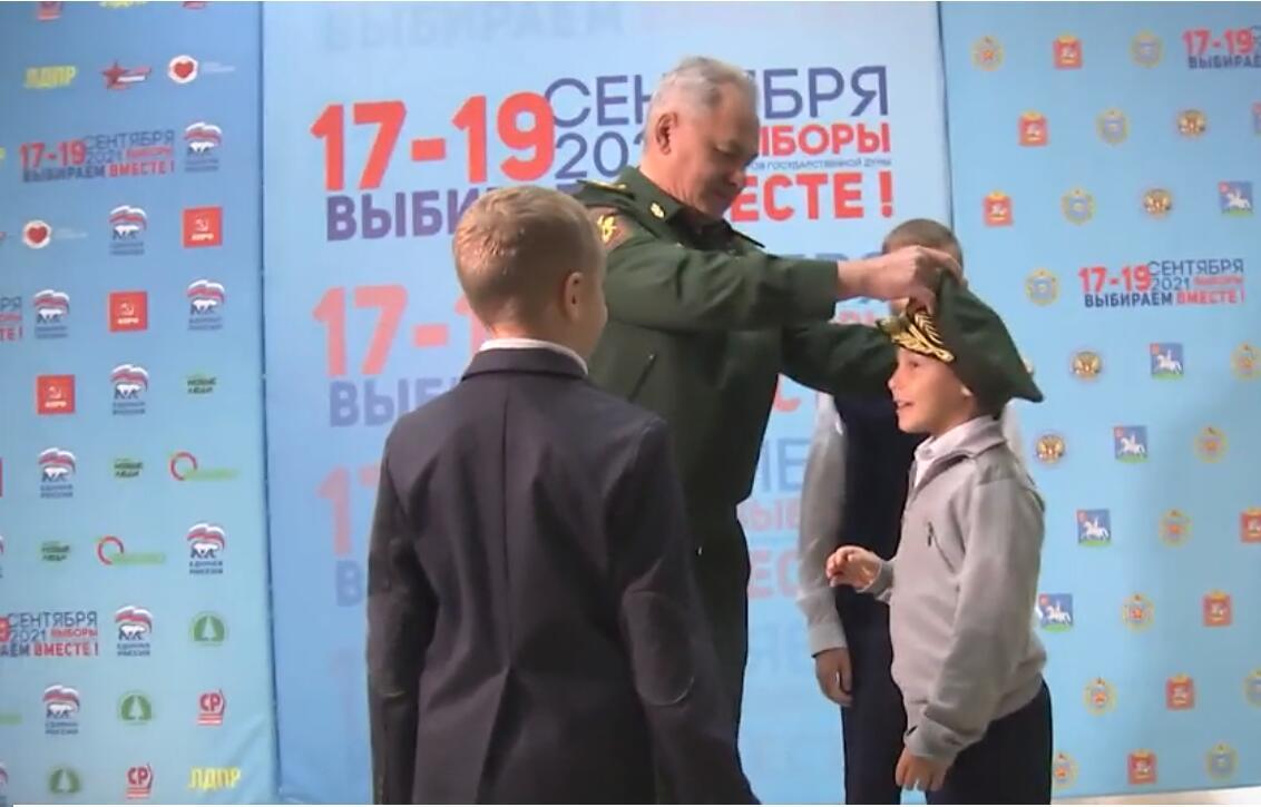 绍伊古给小男孩戴上军帽 图源:俄媒视频截图