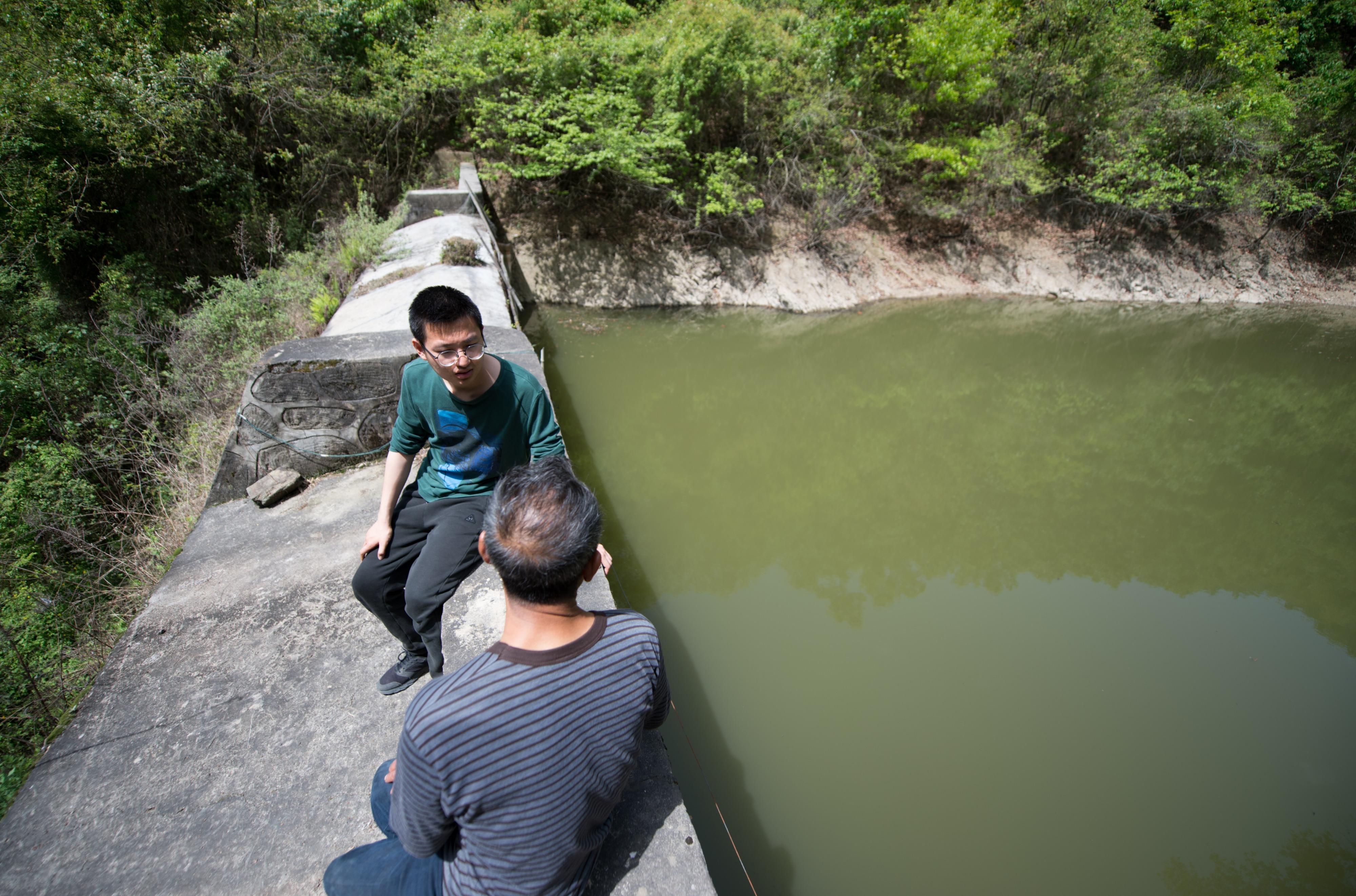 4月16日,在陕西省汉中市西乡县子午镇七星坝村,武轩羽(上)在村民王忠兵承包的鱼塘边与他交谈。