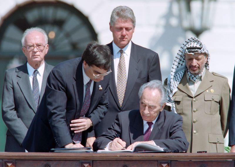 1993年9月13日,美国华盛顿,以色列外交部长西蒙·佩雷斯签署历史性的首个巴以和平协议《巴勒斯坦有限自治原则宣言》(即奥斯陆协议)。后排:以色列总理拉宾、美国总统克林顿、巴解主席阿拉法特。
