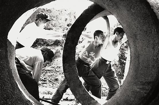1983年,在建设深圳特区的过程中,基建工程兵搬运地下排水管道。图 新华社