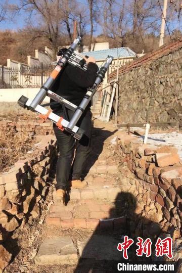雷晨扛着仪器走路。辽宁省地震局供图