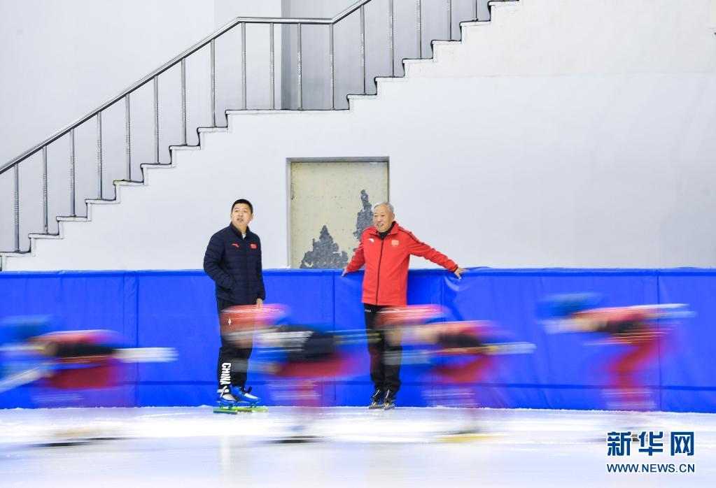 赵伟昌(右)在长春市滑冰馆观看青少年运动员训练(3月30日摄)。新华社记者 许畅 摄