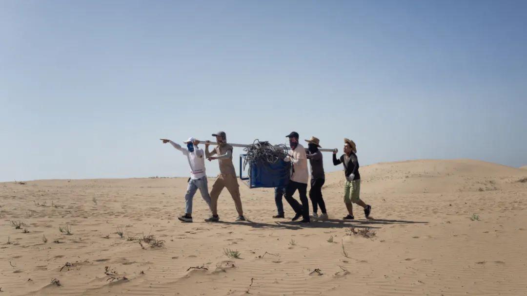 2018年 宁夏银川 场务扛着设备在沙漠中前行
