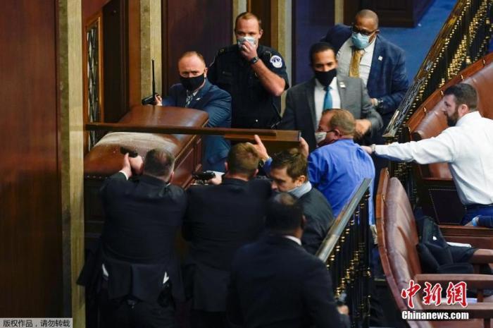 当地时间1月6日,美国国会参众两院召开联席会议期间,特朗普支持者闯入国会大厦引发骚乱,在众议院内,警察隔着门窗持枪与抗议者对峙。