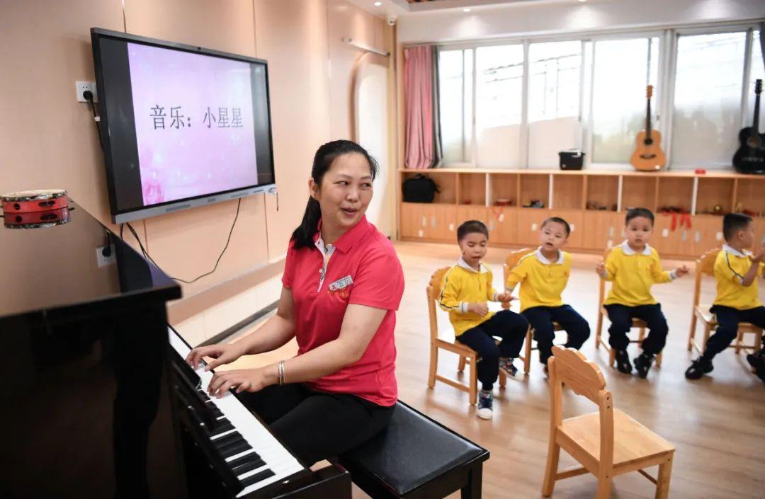 广东茂名市社会福利中心职工李彩玲(左一)在给院内儿童上音乐课(4月27日摄)。