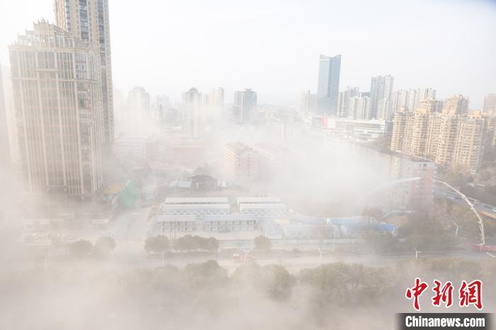 爆破后现场烟尘滚滚,消防队员使用专业设备进行除尘作业。 刘力鑫 摄
