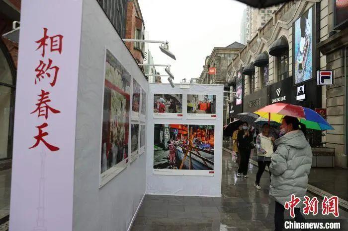 """4月7日,""""相约春天""""抗疫图片展在武汉楚河汉街展出吸引市民参观 张畅 摄"""