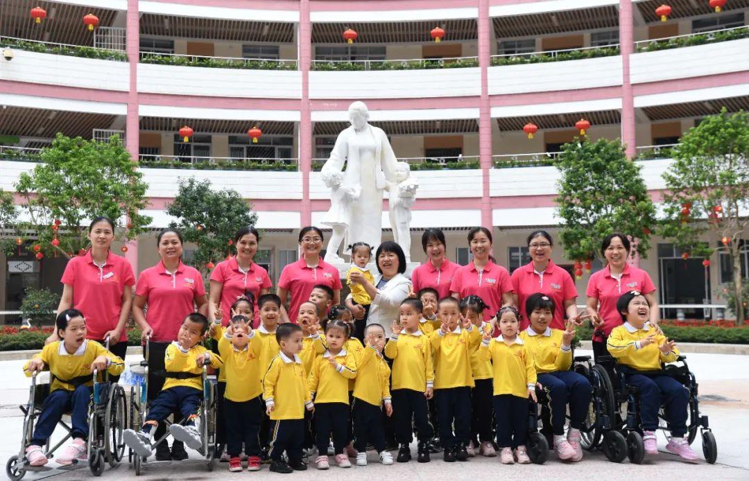 在广东茂名市社会福利中心,主任李兰(后中)和部分职工、儿童合影(4月28日摄)。