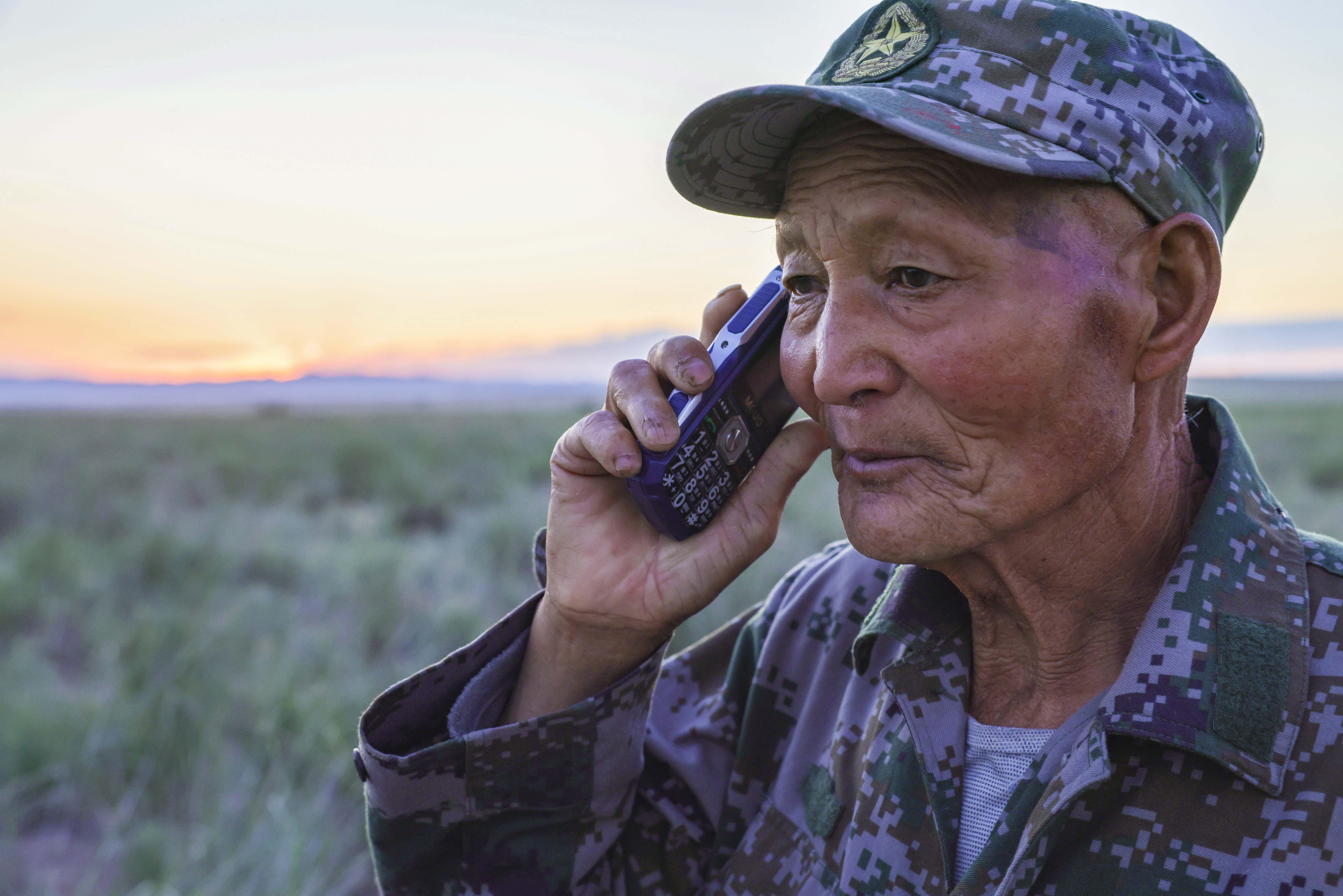 魏德友在放牧赶羊途中用手机和女儿联系(2021年6月8日摄)。新华社记者胡虎虎摄