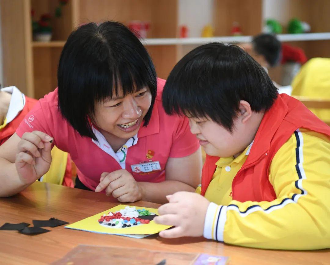 广东茂名市社会福利中心主任李兰(左)在跟院内儿童交流(4月27日摄)。