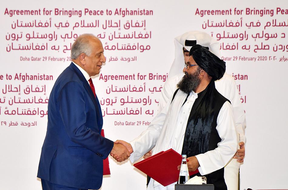 当地时间2020年2月29日,卡塔尔多哈,美国阿富汗和解特别代表扎尔迈·哈利勒扎德和塔利班政治事务领导人巴拉达尔(右)签署和平协定。