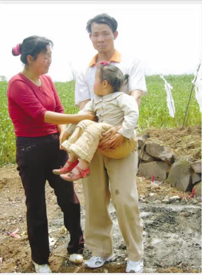邓率夫妇在三个孩子坟前.jpg
