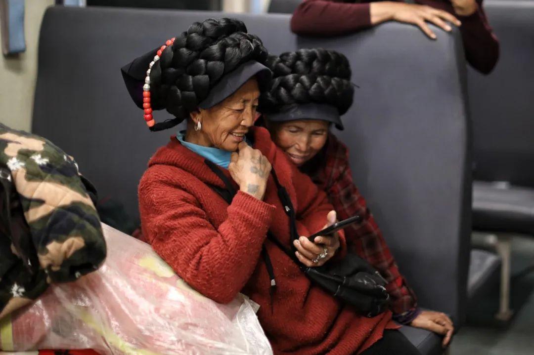 2月26日,5634次列车上的彝族乘客在用手机看短视频。新京报记者 王嘉宁 摄