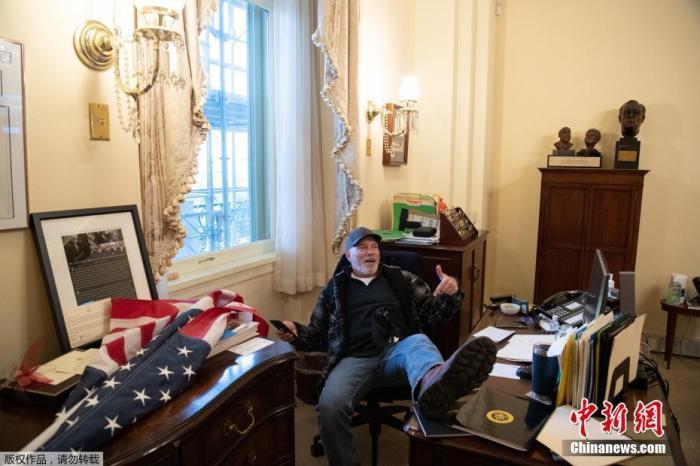 图为抗议示威期间,特朗普支持者坐在美国众议院议长佩洛西办公室内。