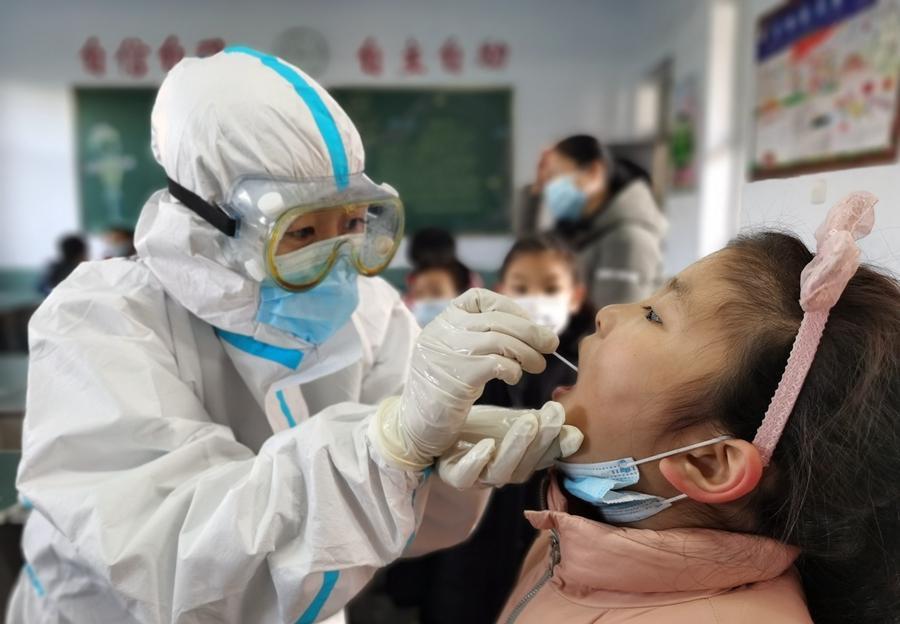 1月6日,在河北省邢台市南园路小学,医务人员为学生进行核酸检测采样。图/网络