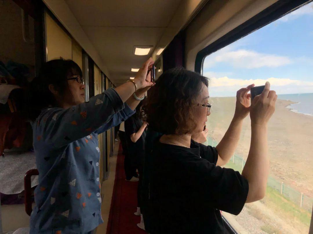 6月4日,Z21次列车上,旅客不舍错过窗外每一处风景。新京报记者 杜寒三 摄