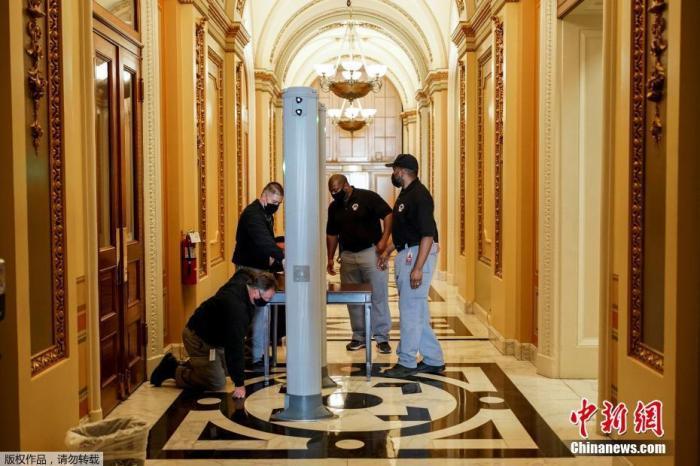 当地时间2021年1月12日,美国首都华盛顿,美国会大厦的安保和修复工作持续进行中。美国司法部首次对两名与国会大厦抗议冲突事件相关的犯罪嫌疑人提出联邦大陪审团起诉,两人均于上周被捕,他们的刑事指控在抗议冲突事件后不久就被公诸于众。在这些人根据刑事控诉被捕后,起诉书使他们的指控正规化。图为当地时间1月12日,美国华盛顿,安全人员在美国国会大厦众议院会议厅入口处安装安全门。