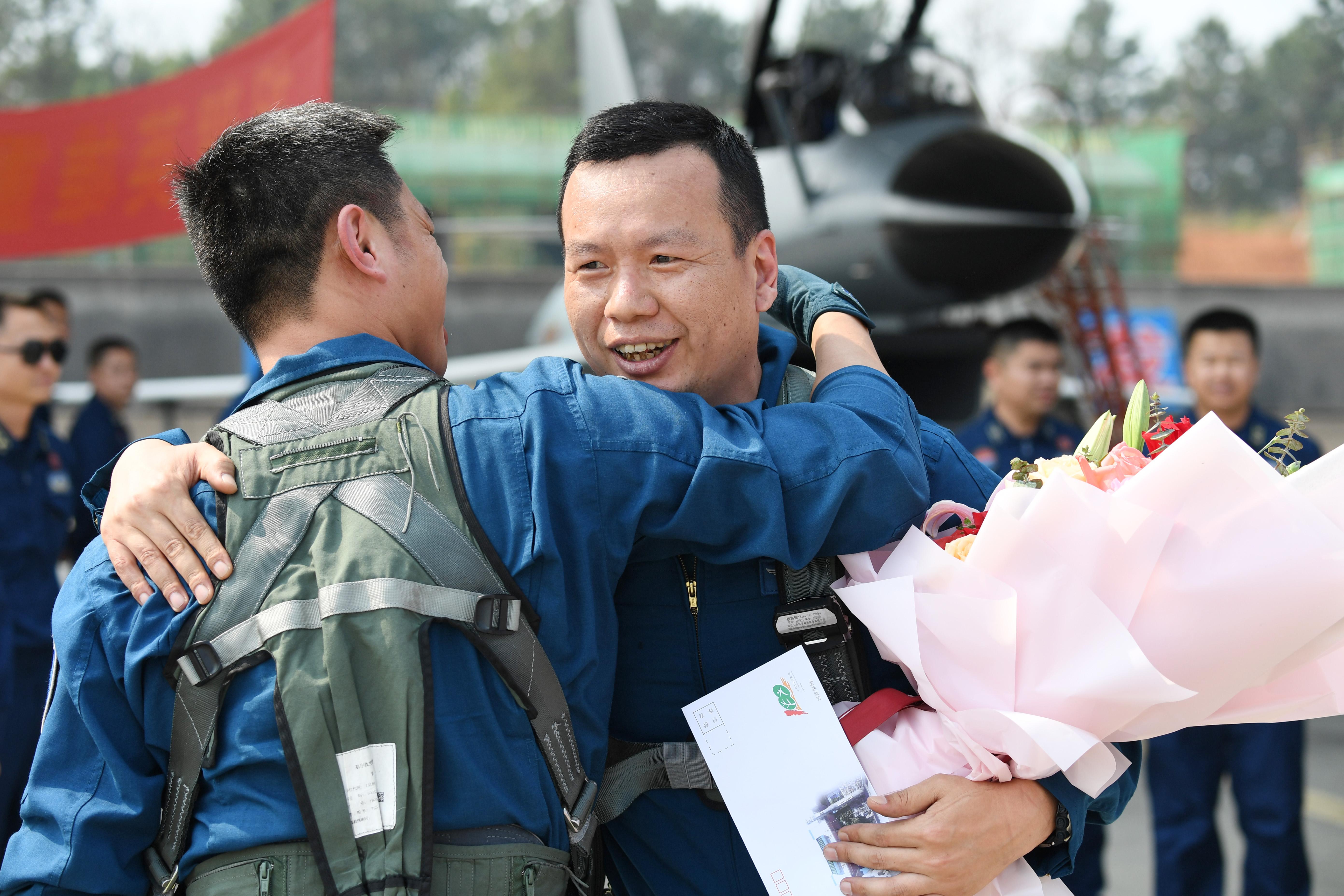 ↑2月23日,复飞重返战位的一等功空军飞行员王建东完成飞行计划后,与战友拥抱庆祝。唐俊 摄