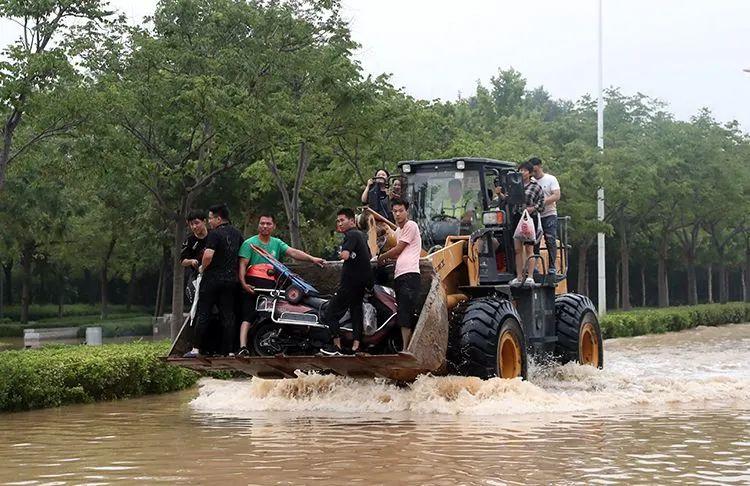 ▲7月21日,郑州,市民王先生驾驶挖掘机满载被困群众。他自发前往积水区,已转移群众六十余名。