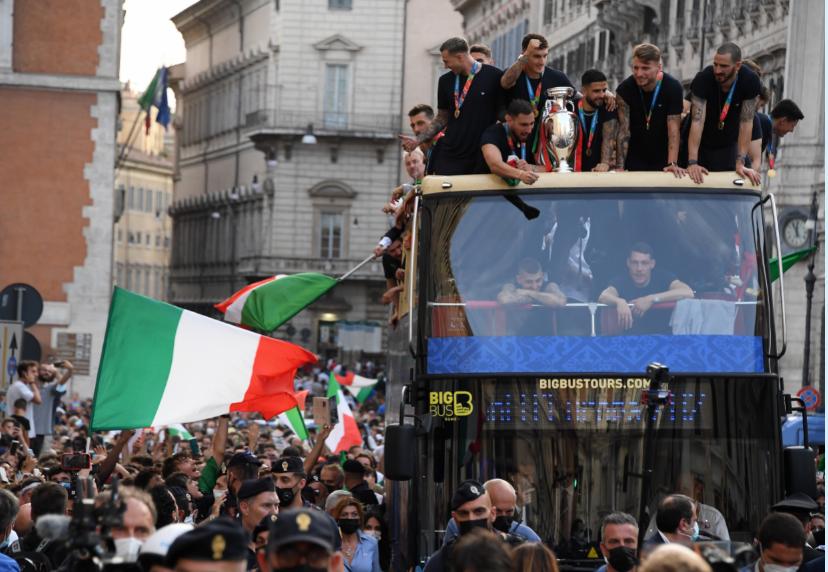 当地时间7月12日,意大利队成员在罗马参加巡游活动,与球迷共同庆祝欧洲杯夺冠。图/新华社