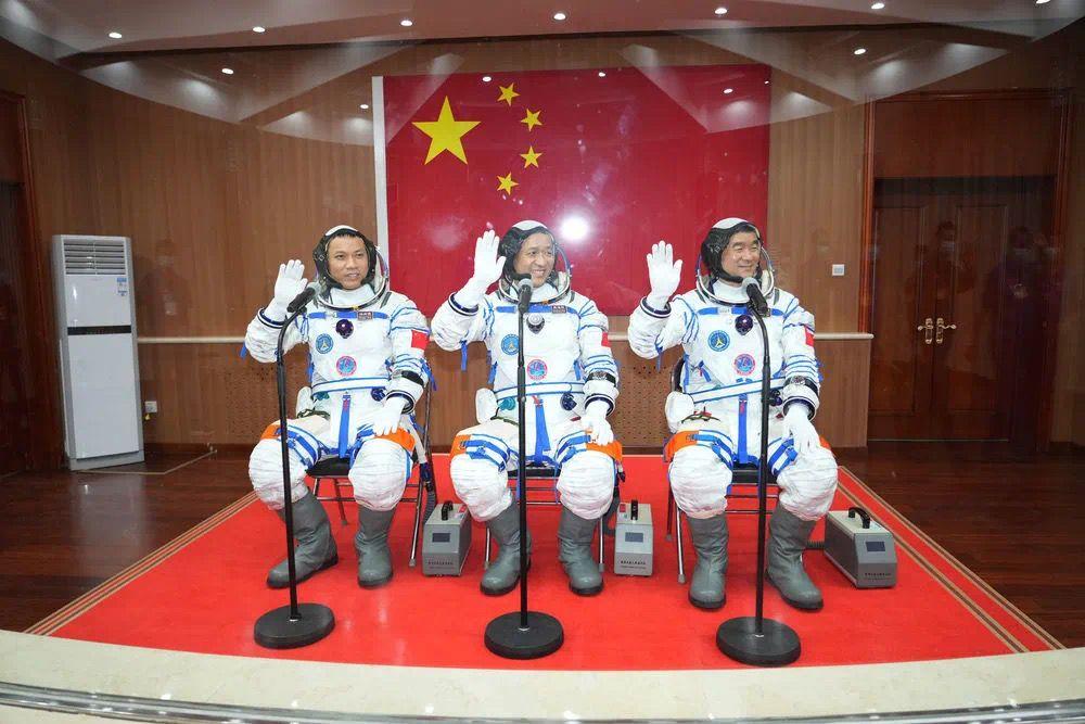 6月17日,航天员聂海胜(中)、刘伯明(右)和汤洪波在出征前挥手致意。图片来源:新华社