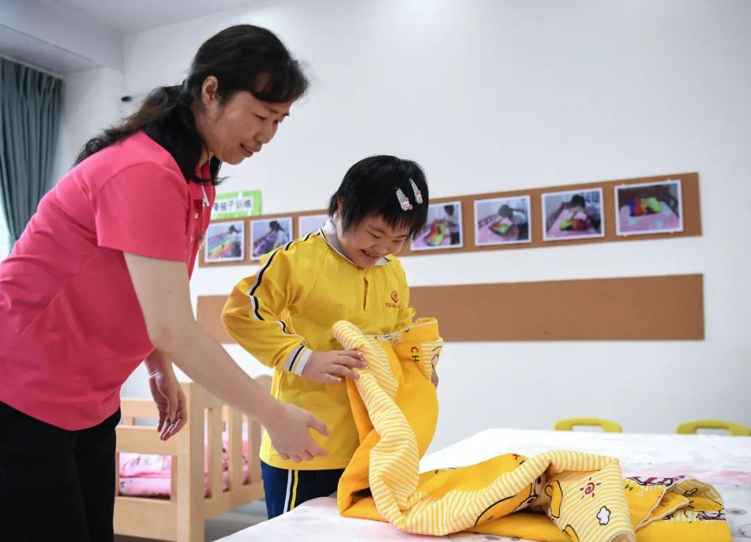 在广东茂名市社会福利中心,工作人员倪水清(左)在教院内儿童叠被子(4月27日摄)。
