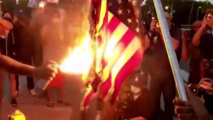 现场:美国抗议者想焚烧国旗 但点了半天没烧起来