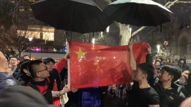"""中国留学生包围""""港独""""游行:雨中齐唱国歌,给国旗打伞"""