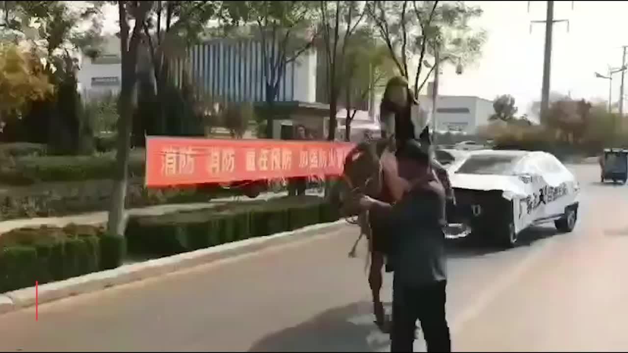 新型维权方式?发动机炸了要自费修 女子骑马拉奔驰游街维权