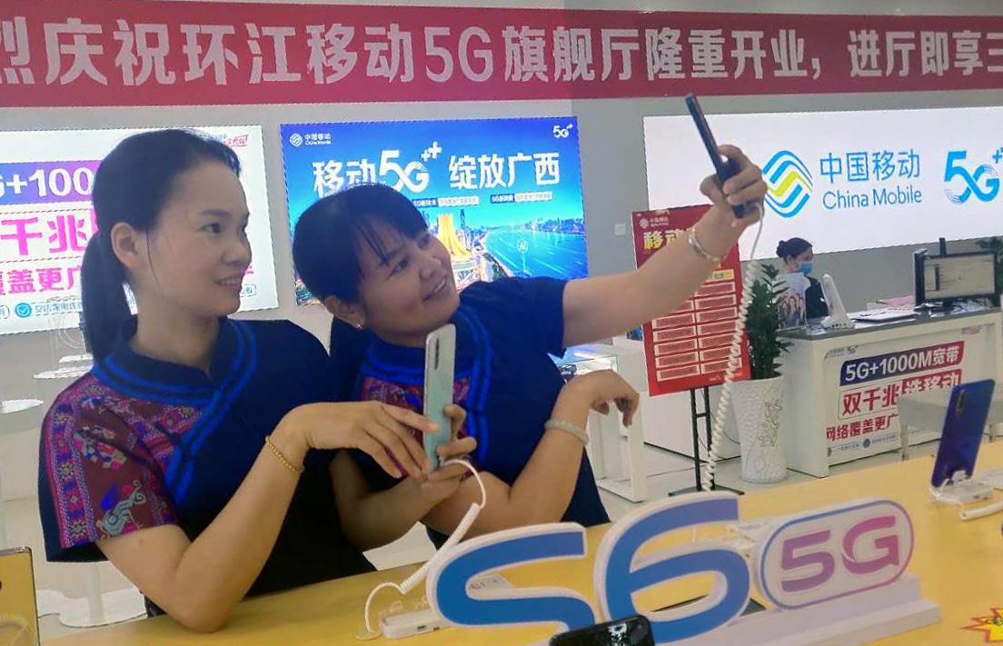 目前,广西移动不仅在毛南族自治县全县覆盖了4G网络,还在当地的重要区域覆盖了5G网络。图中的毛南族群众在环江移动5G旗舰厅选购5G手机。(谭施莲摄影)