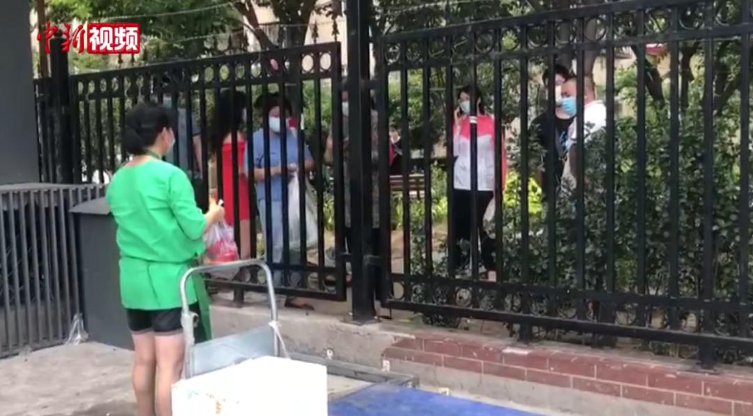 居民只能隔着栅栏购买食材。视频截图