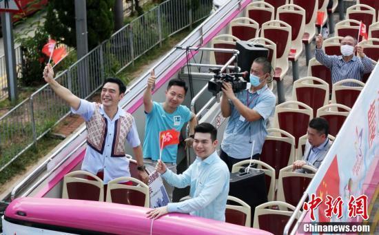 """7月1日,香港各界庆典委员会在中环码头举行""""庆香港回归 贺国安立法""""启动礼。图为著名艺人钟镇涛等参加花车巡游。"""