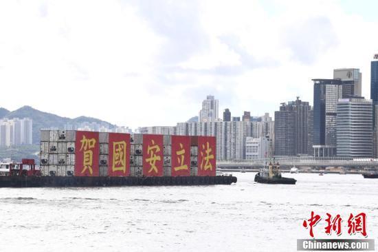 """7月1日,百艘渔船于香港维港巡游,""""庆香港回归""""""""贺国安立法""""的巨幅标语矗立船舷,吸引维港两岸的市民围观及拍照。 中新社记者 李志华 摄"""