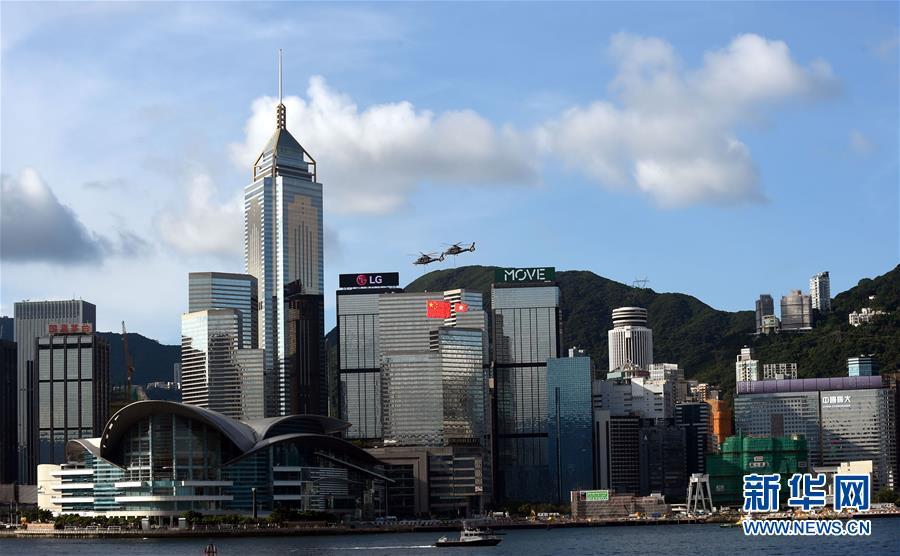 7月1日,香港特区政府在金紫荆广场举行升旗仪式,庆祝香港回归祖国20周年。这是两架分别悬挂中华人民共和国国旗、香港特区区旗的直升机从香港会展中心上空飞过。新华社记者 卢炳辉 摄