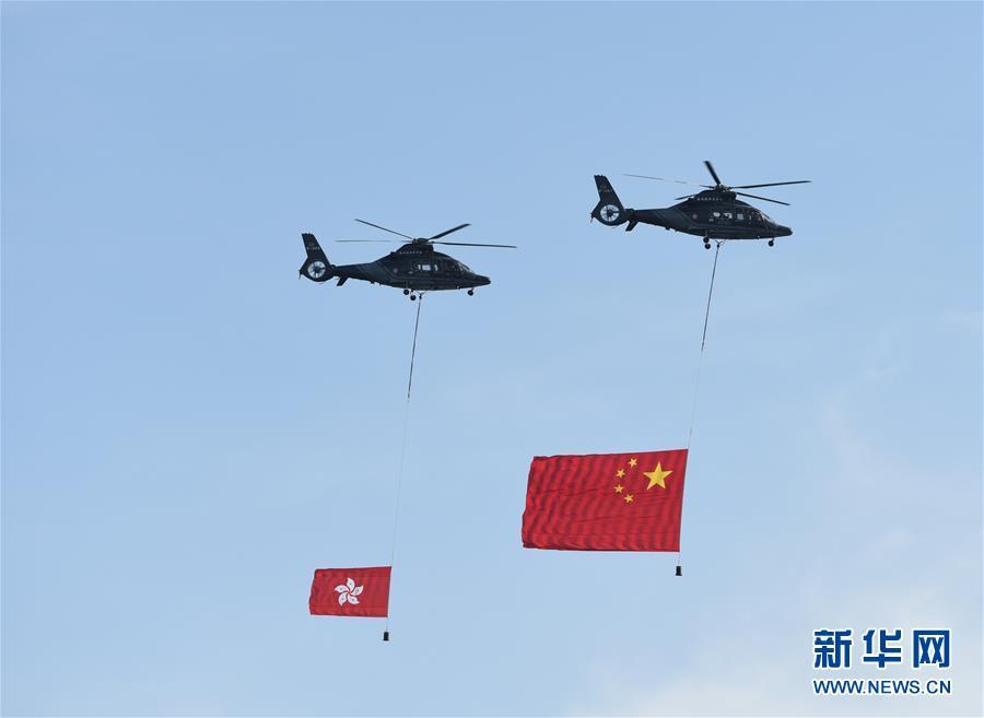 7月1日,香港特区政府在金紫荆广场举行升旗仪式,庆祝香港回归祖国20周年。这是两架分别悬挂中华人民共和国国旗、香港特区区旗的直升机从空中飞过。新华社发(王申 摄)