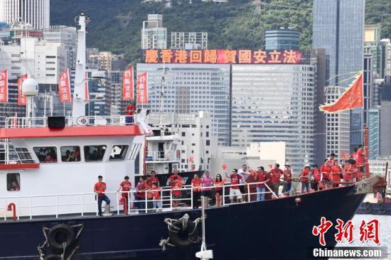 """7月1日,市民于渔船上庆祝。百艘渔船于香港维港巡游,""""庆香港回归""""""""贺国安立法""""的巨幅标语矗立船舷,吸引维港两岸的市民围观及拍照。 中新社记者 李志华 摄"""