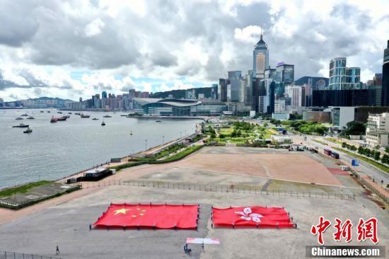 """7月1日,香港各界庆典委员会在中环码头举行大型""""庆香港回归 贺国安立法""""活动。图为欢庆者在中环展示国旗和区旗。 中新社记者 洪帆 摄"""